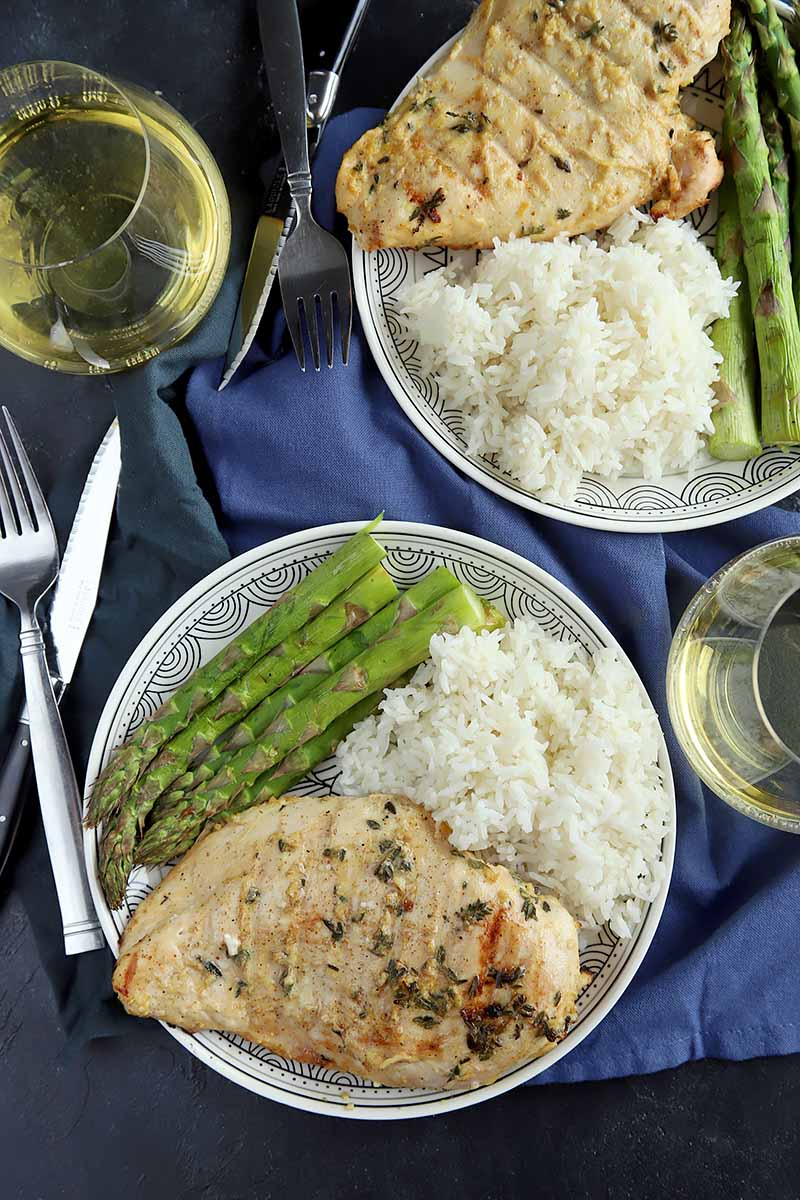 Vertical top-down image of two plates with poultry, asparagus, and rice on a blue napkin.