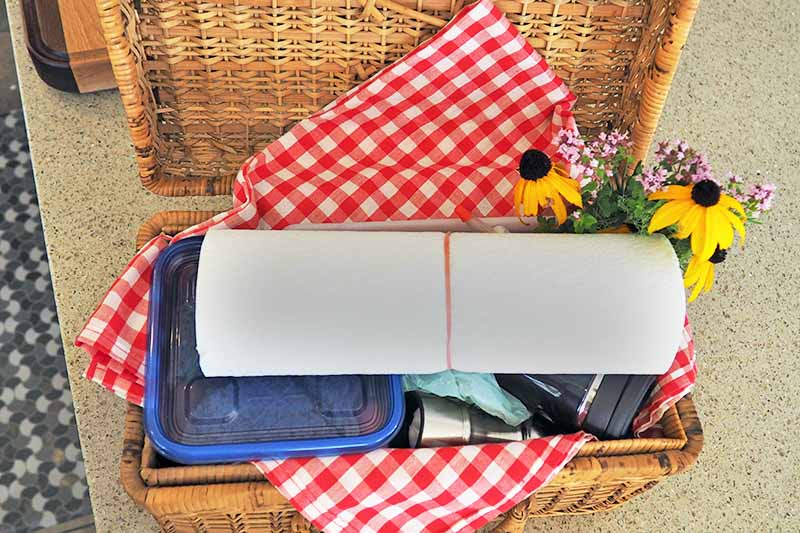 A picnic basket holds a checkered blanket, snap lock containers, paper towels, and other picnic essentials.