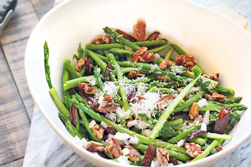 Horizontal overhead image of a white ceramic bowl of asparagus with walnuts, dried fruit, and freshly grated cheese, on a gray and white marble slab on top of a brown wood surface.