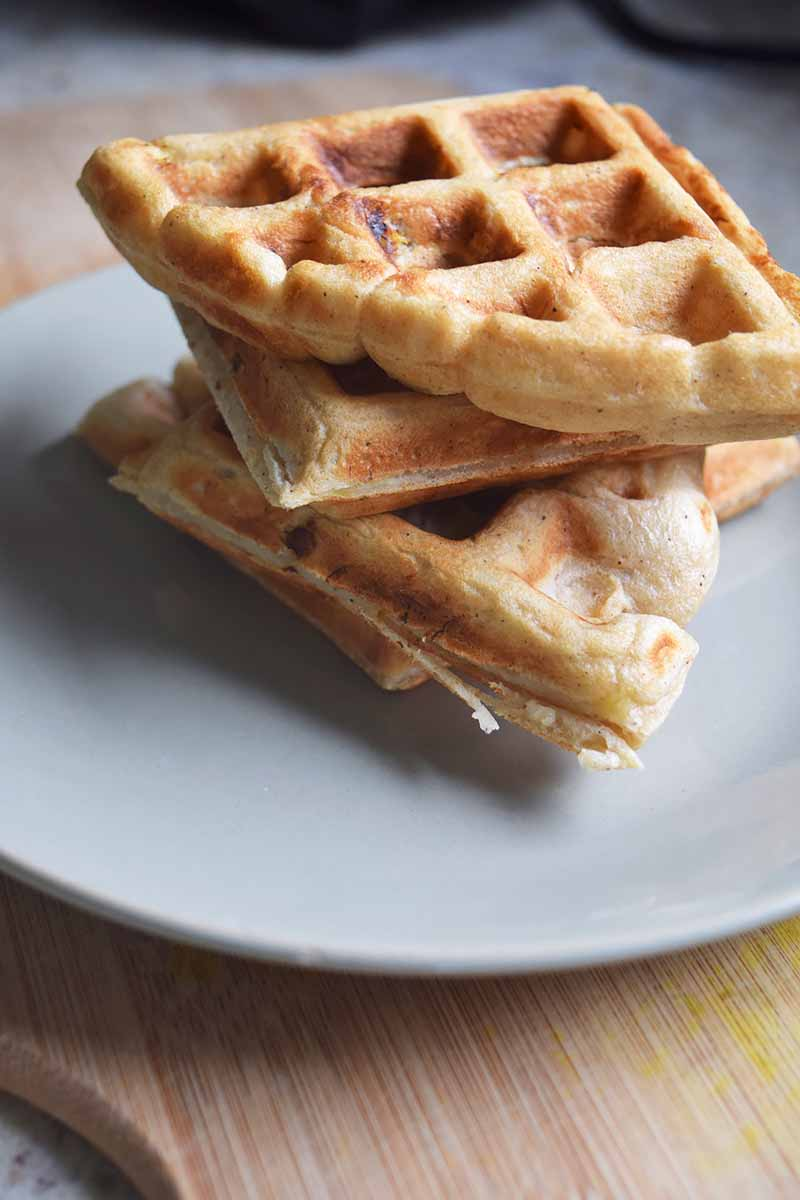 Vertical image of a plain stack of three quartered waffles on a white plate.