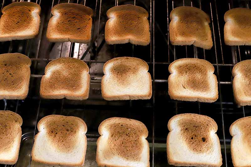 Vertical image of three rows of white bread toasted golden brown to various degrees, on a metal baking rack in an oven.