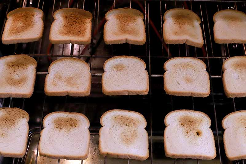 White bread ranging from toasted to lightly browned, on a metal rack in a large appliance.