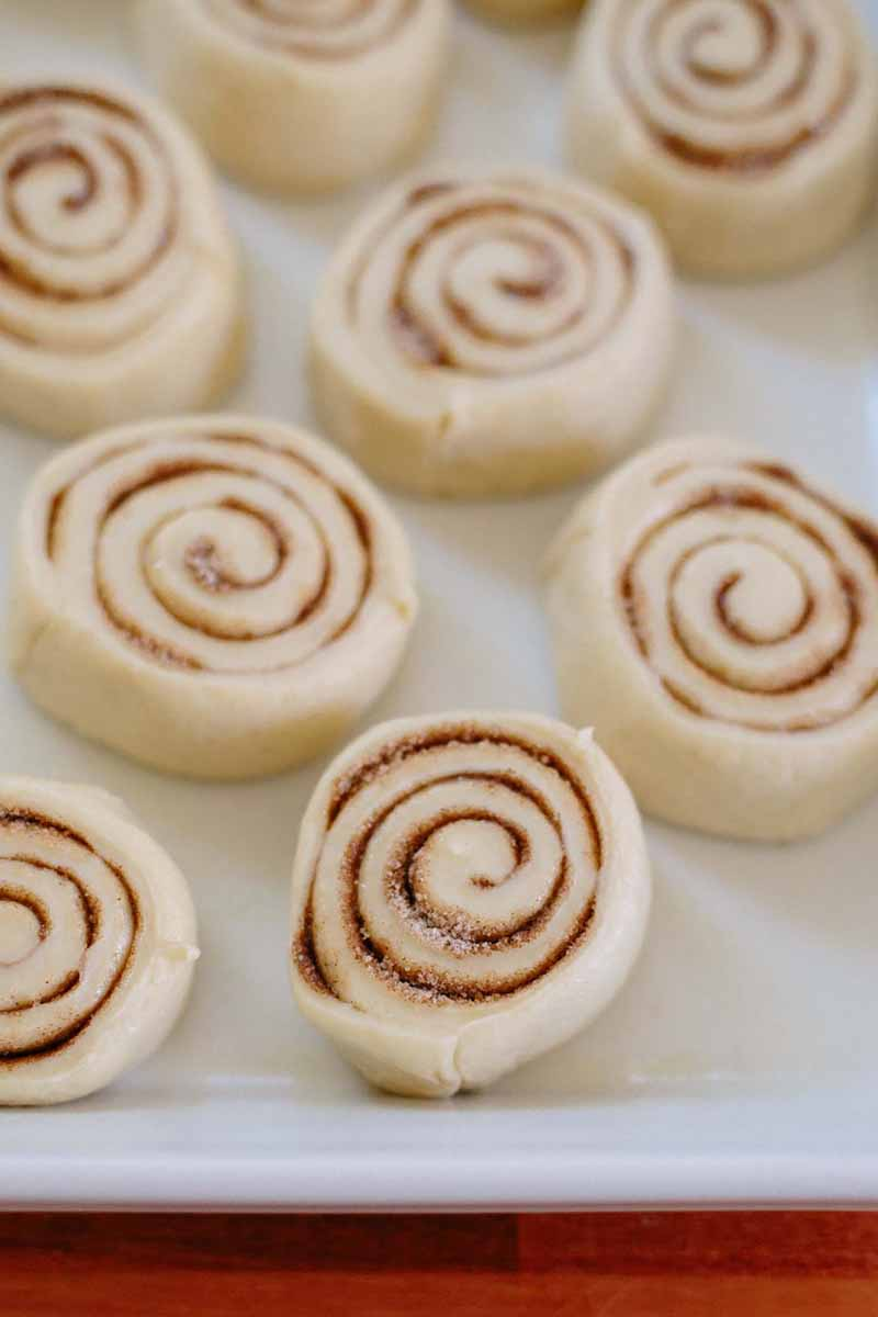 Vertical image of unbaked cut cinnamon rolls on a baking sheet.