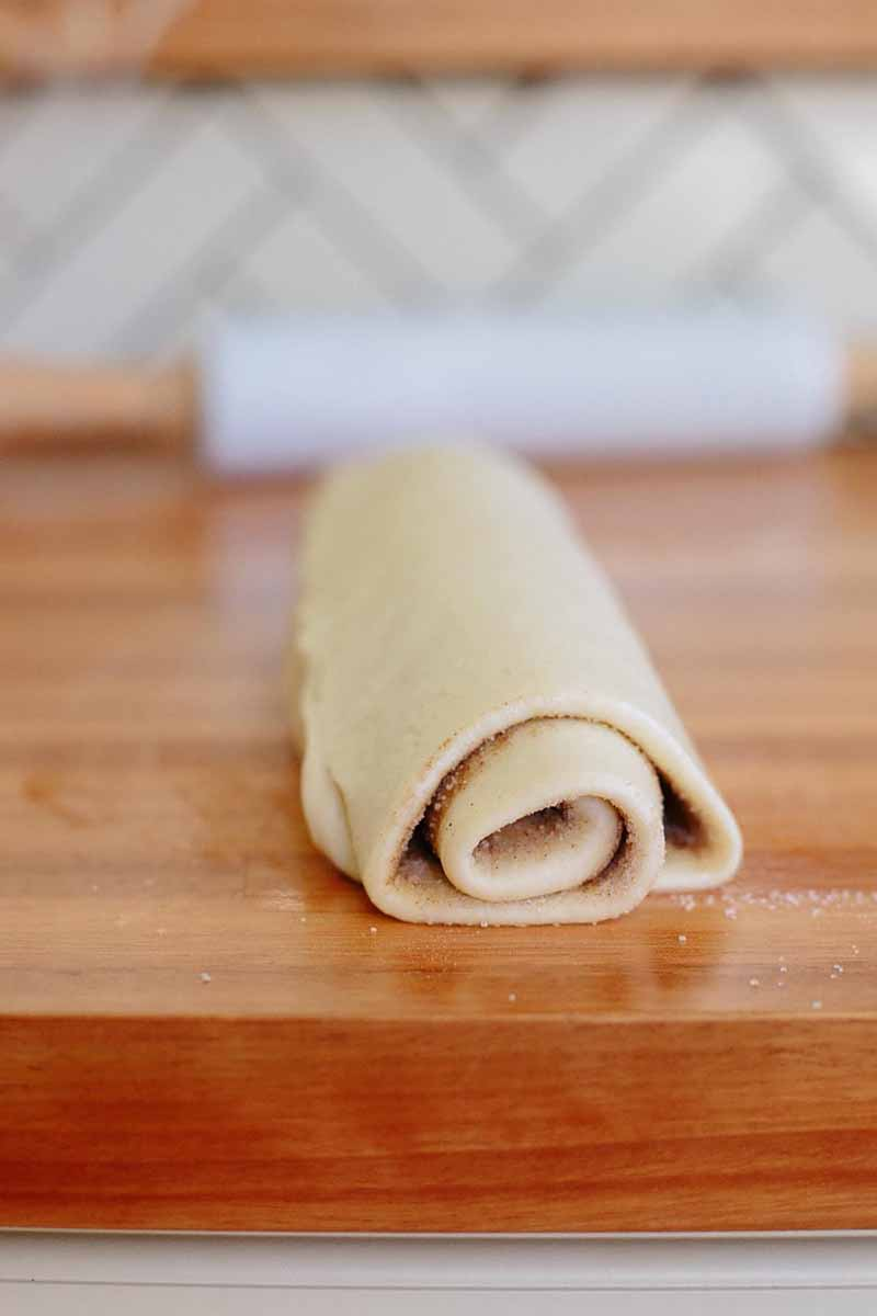 Vertical image of rolled raw cinnamon roll dough on a wooden table with a rolling pin in the background.