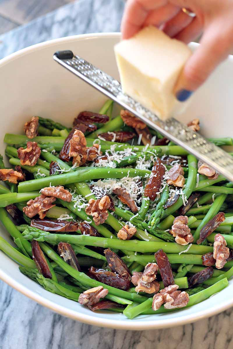 Vertical image of a hand with manicured and polished fingernails grated a block of cheese with a microplane onto the asparagus salad below, in a white bowl on top of a gray marble surface.