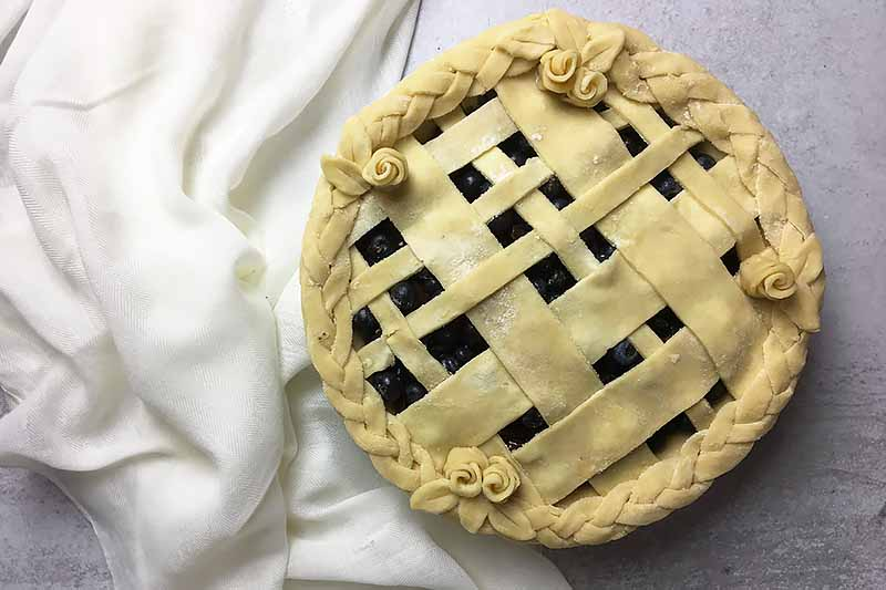 Horizontal image of a whole unbaked decorated pie on a white towel.