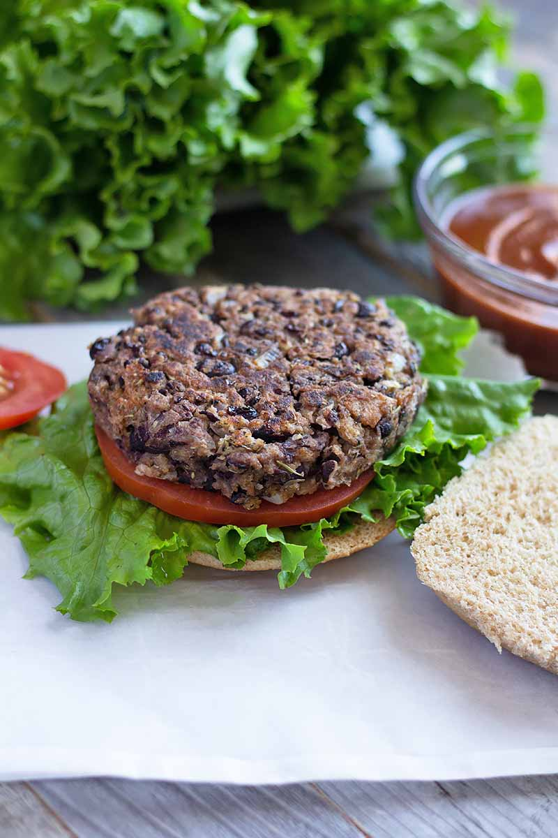 Vertical image of an open-faced black bean burger with tomatoes and lettuce.
