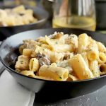 Horizontal image of a black bowls with creamy pasta, with a glass of white wine.