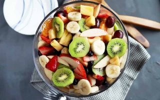 Horizontal top-down image of a big glass bowl with cut kiwi, banana, pineapple, strawberries, and grapes.