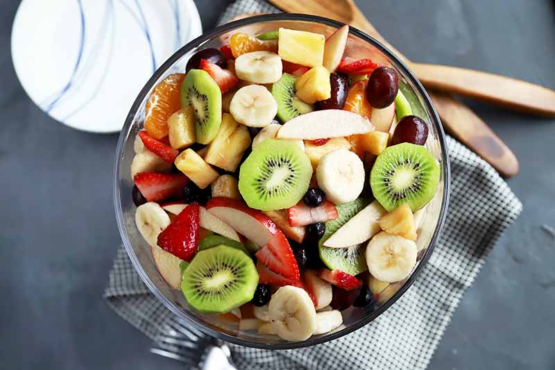 Horizontal top-down image of a big glass bowl with cut kiwi, banana, pineapple, strawberries, and grapes.