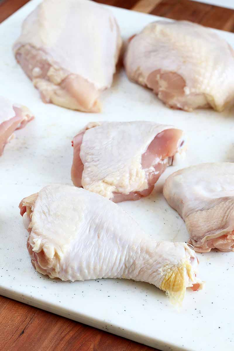 Vertical image of different raw pieces of poultry on a white cutting board.