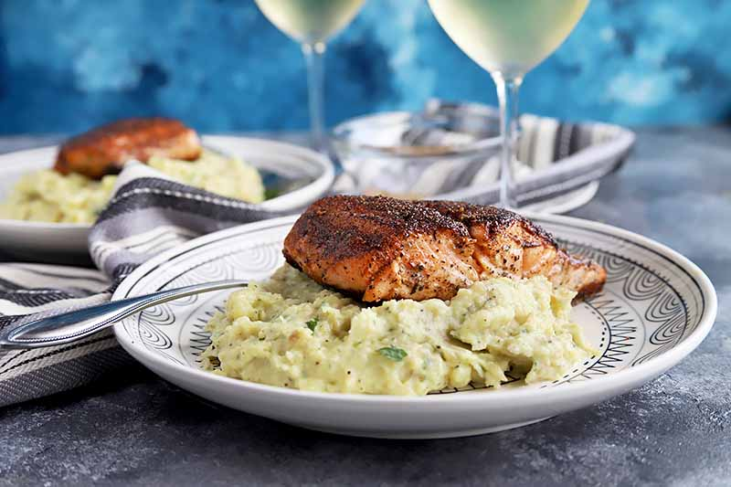 Horizontal image of a cooked salmon fillet on mashed potatoes in front of glasses of white wine.