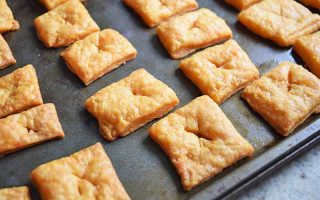 Closeup of square cheese crackers arranged in rows on a metal baking sheet.