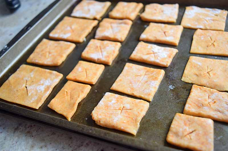 Horizontal image of portioned cheese cracker dough lightly coated with flower, arranged on a metal baking sheet pan on a kitchen counter.
