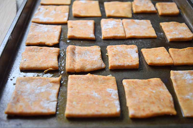 Raw cheddar dough squares arranged on a baking sheet.