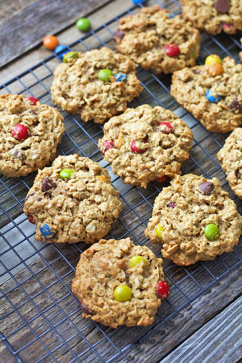 Vertical oblique overhead image of cookies studded with rainbow-colored M&Ms, cooling on a wire rack on top of a wood surface.