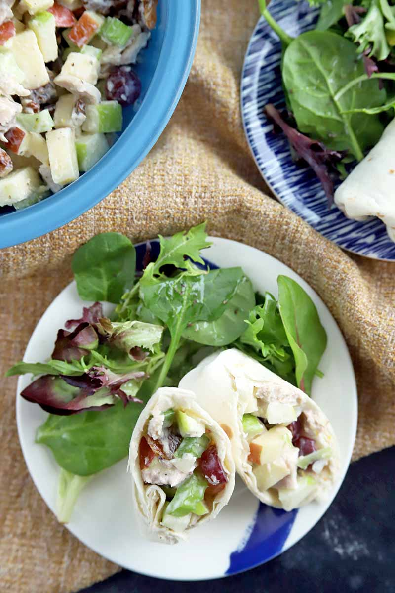 Overhead vertical shot of two plates of chicken salad wraps with green salads, on a gathered piece of light brown burlap with a light blue glass bowl filled with more of the dish, on a dark gray surface with white streaks.