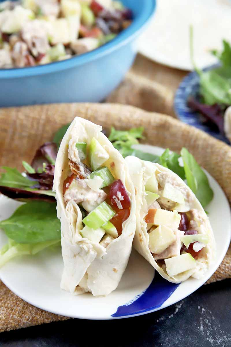 Vertical image of a Waldorf chicken salad wrap in a flour tortilla, cut in half and displayed on a blue and white plate with leafy greens, on a piece of burlap, with a blue bowl containing more of the salad and another plate in the background, on a gray surface.