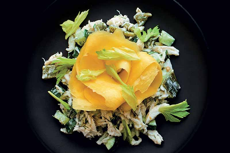 Overhead horizontal image of a salad made with crab, shaved mango, dill, and poblano pepper, on a black plate against a black background.
