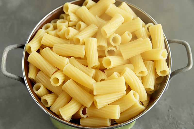 Horizontal image of a bowl of cooked rigatoni.