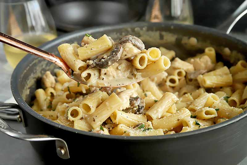 Horizontal image of a spoon holding a creamy chicken and mushroom pasta dish in a skillet.