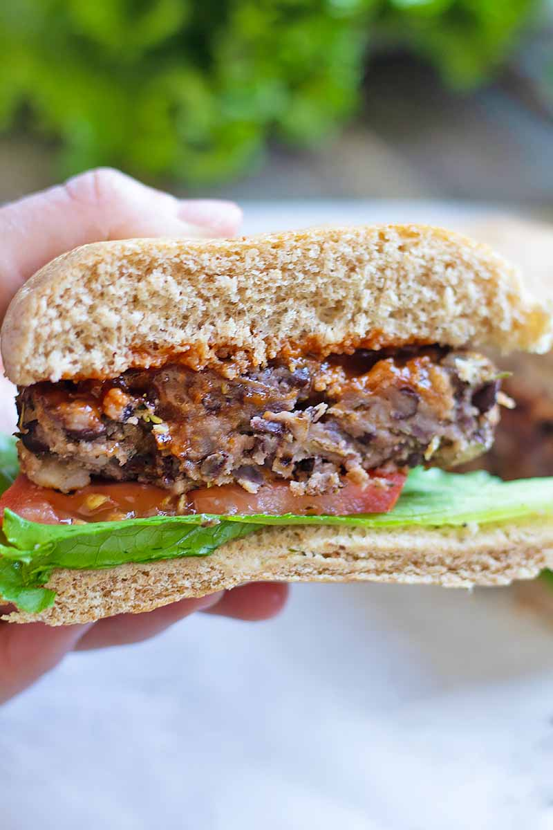 Vertical close-up image of a halved veggie burger with a hand holding it.