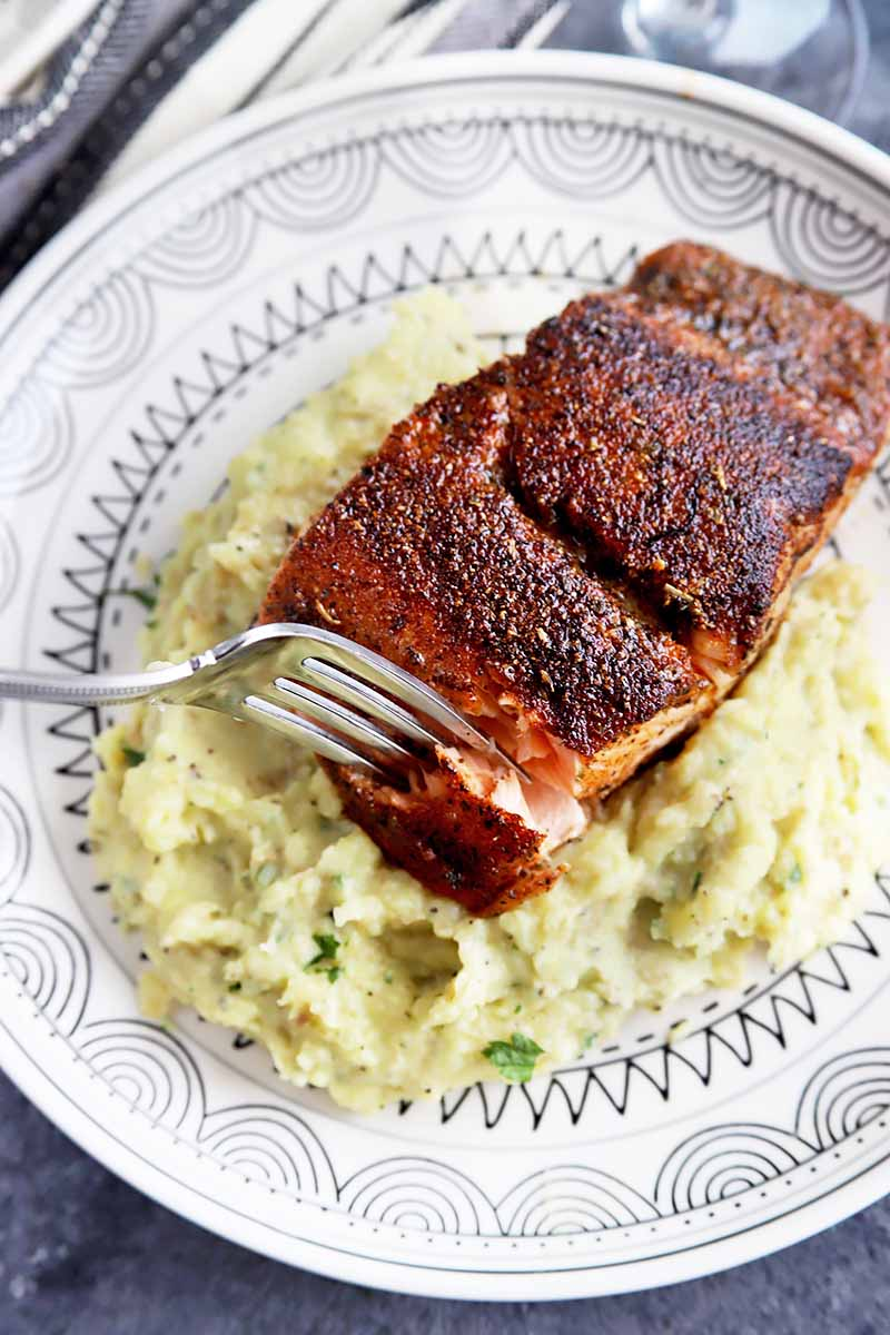 Vertical image of a fork piercing a blackened piece of salmon over mashed potatoes on a white plate with a blue pattern.