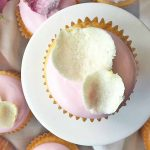 Horizontal image of a pink cupcake on a white stand with white petals.