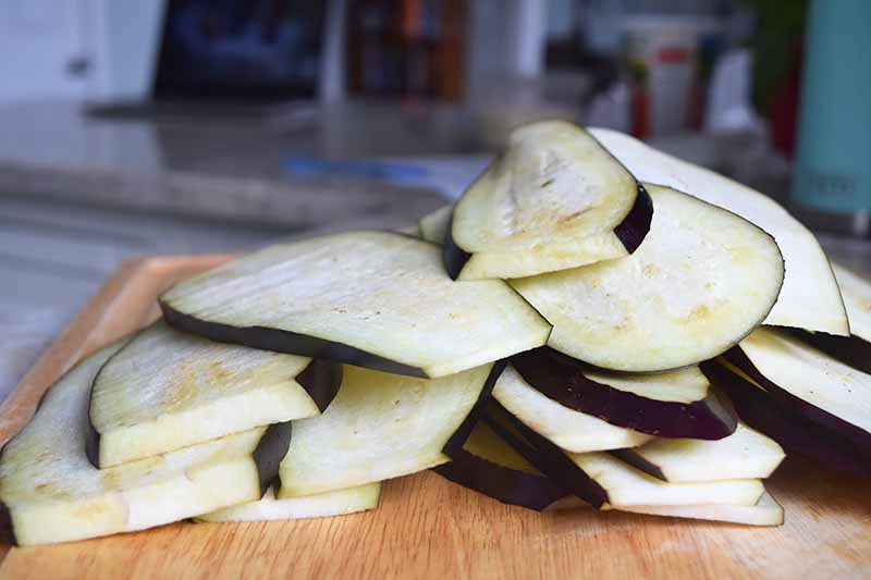 Horizontal image of a wooden cutting board topped with a mound of sliced eggplant.