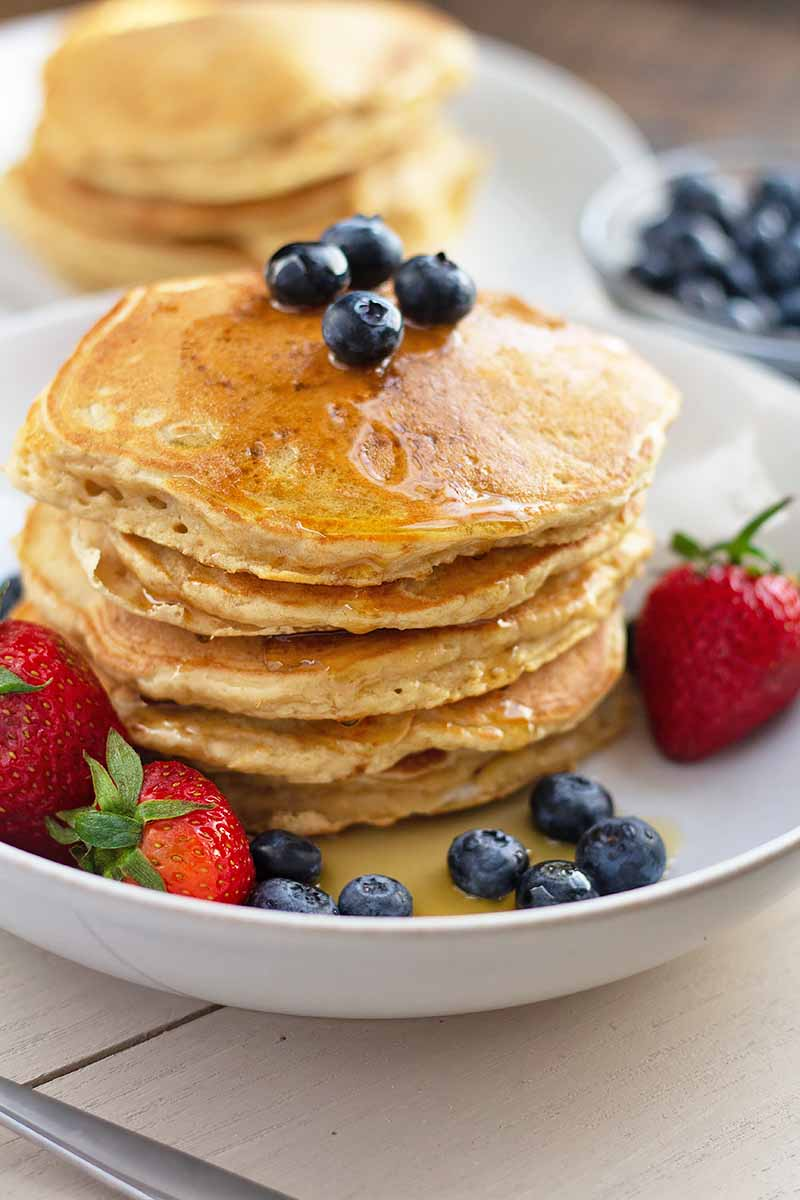Vertical image of a stack of flapjacks on a white dish with berries, topped with syrup and blueberries.