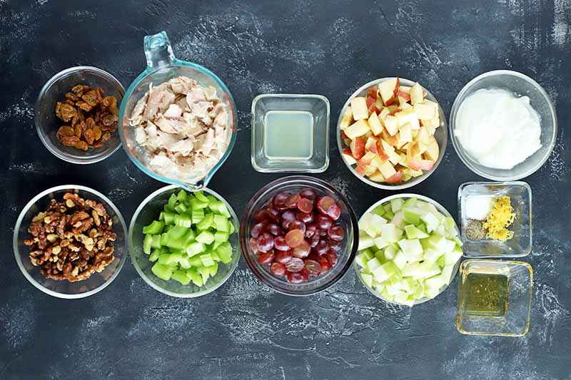Overhead shot of the ingredients required to make chicken Waldorf salad in small round and square bowls, including raisins, walnuts, chicken, celery, grapes, lemon juice, mayonnaise, seasonings, chopped apples, lemon zest, and olive oil.