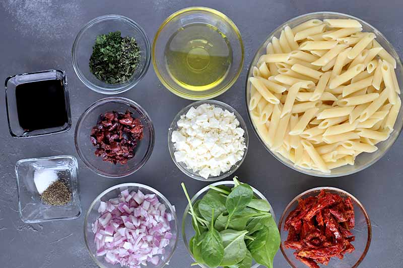 Overhead image of two small square glass dishes of vinegar and spices, seven small round glass bowls of chopped herbs, dried cranberries, chopped purple onion, oil, crumbled feta, baby spinach, and chopped sun-dried tomatoes, and a larger round glass bowl of cooked penne, on a gray surface.