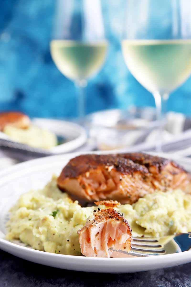 Vertical image of a plate of mashed potatoes with salmon and a fork holding a piece of salmon with wine glasses and white wine in front of a blue background.