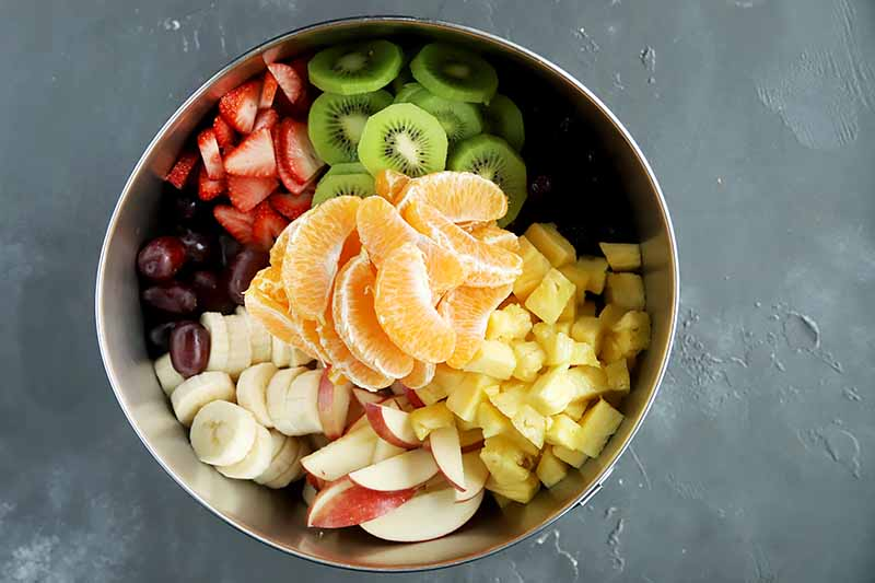 Horizontal image of neatly placed fresh fruit in a metal bowl.