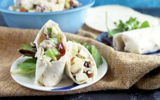 Horizontal image of two chicken salad wraps on plates, with the one in the foreground cut in half to show the filling inside, with leafy greens to the side of each plate, and a glass bowl of more of the salad to the left of a stack of flour tortillas in shallow focus in the background, on a folded piece of light brown burlap on top of a dark gray surface.