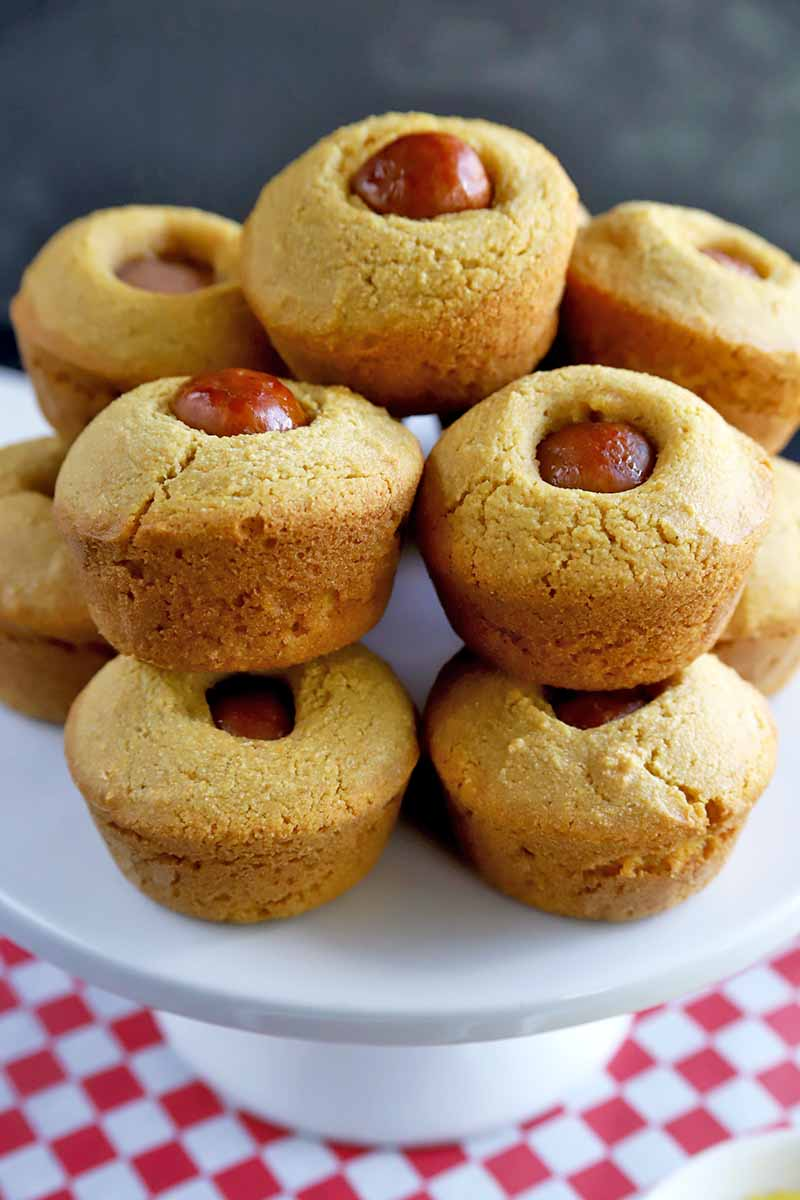 About a dozen corn muffins with a piece of hot dog at the center of each, arranged on a white ceramic cake stand, with a red and white checkered paper liner at the base, against a gray background.