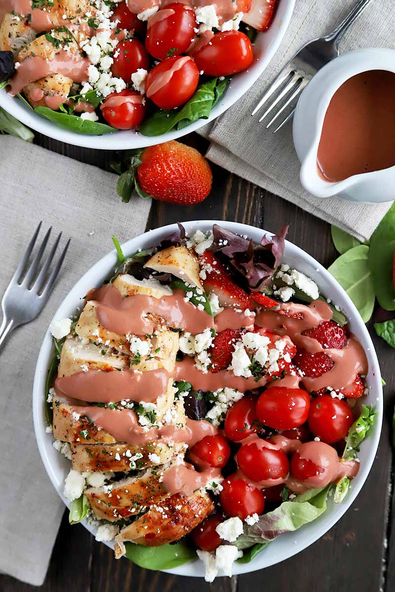 Vertical top-down image of two plates of chicken salad with grape tomatoes and a pink dressing, next to off-white napkins with metal forks and a dressing vessel.