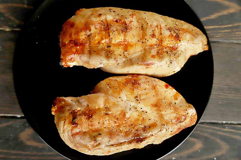 Horizontal image of a black plate with two whole grilled chicken breasts.