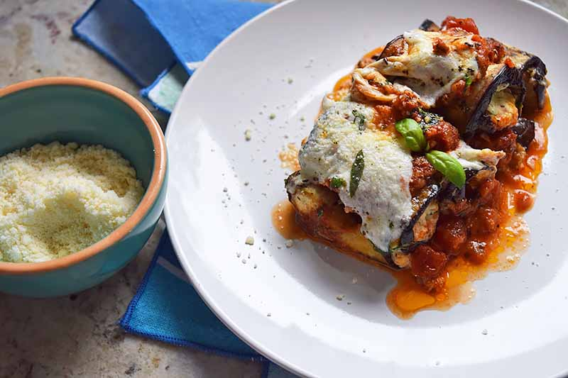 Horizontal image of a serving of an eggplant casserole on a white plate next to a bowl of grated cheese.