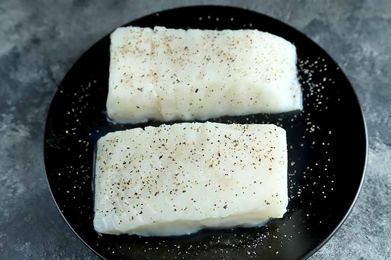 Two raw halibut fillets sprinkled with salt and pepper, on a white plate on a gray mottled background.