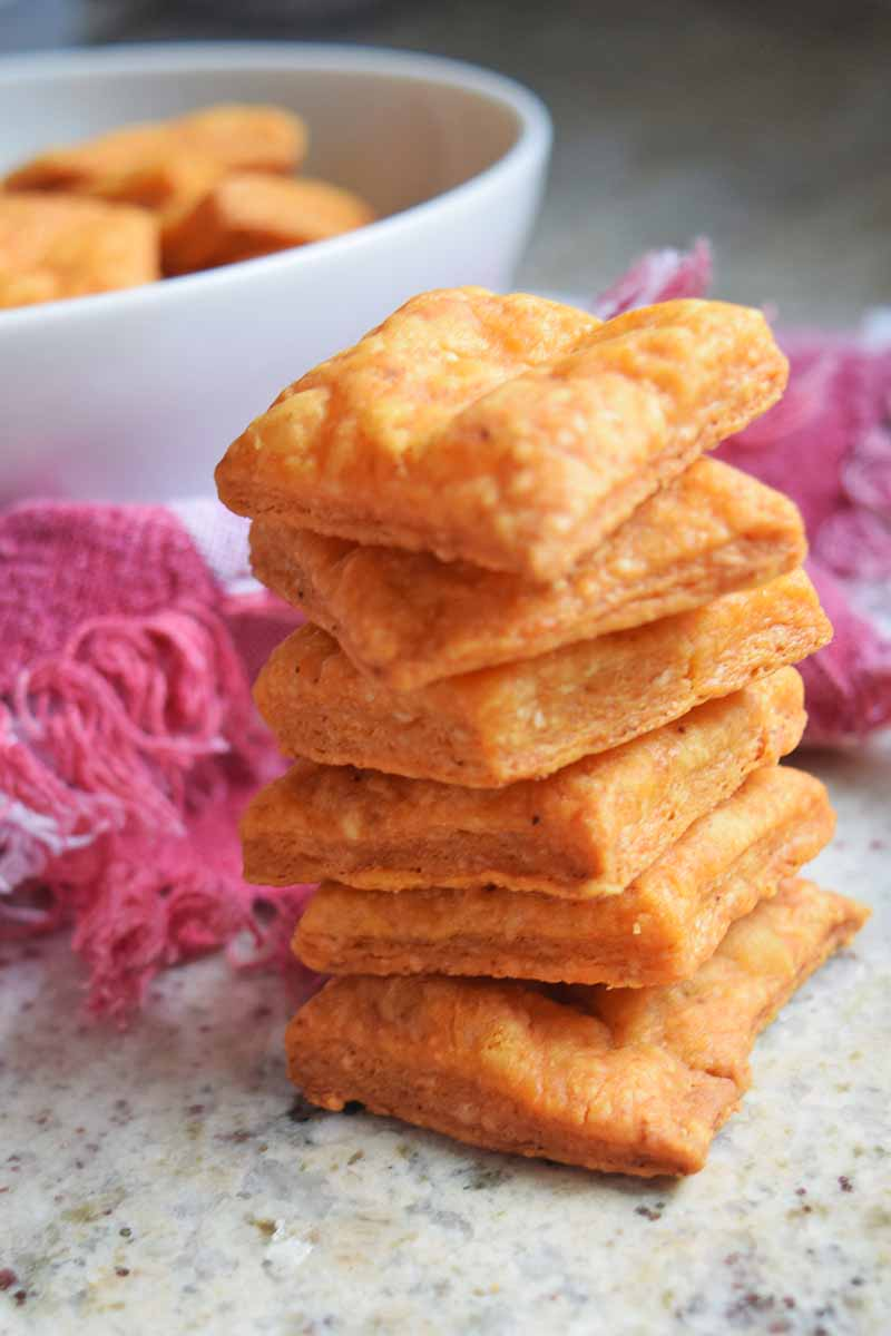 Vertical image of a stack of six homemade cheese crackers on a countertop with a magenta cloth with fringe and a white bowl of more of the snacks in soft focus in the background.