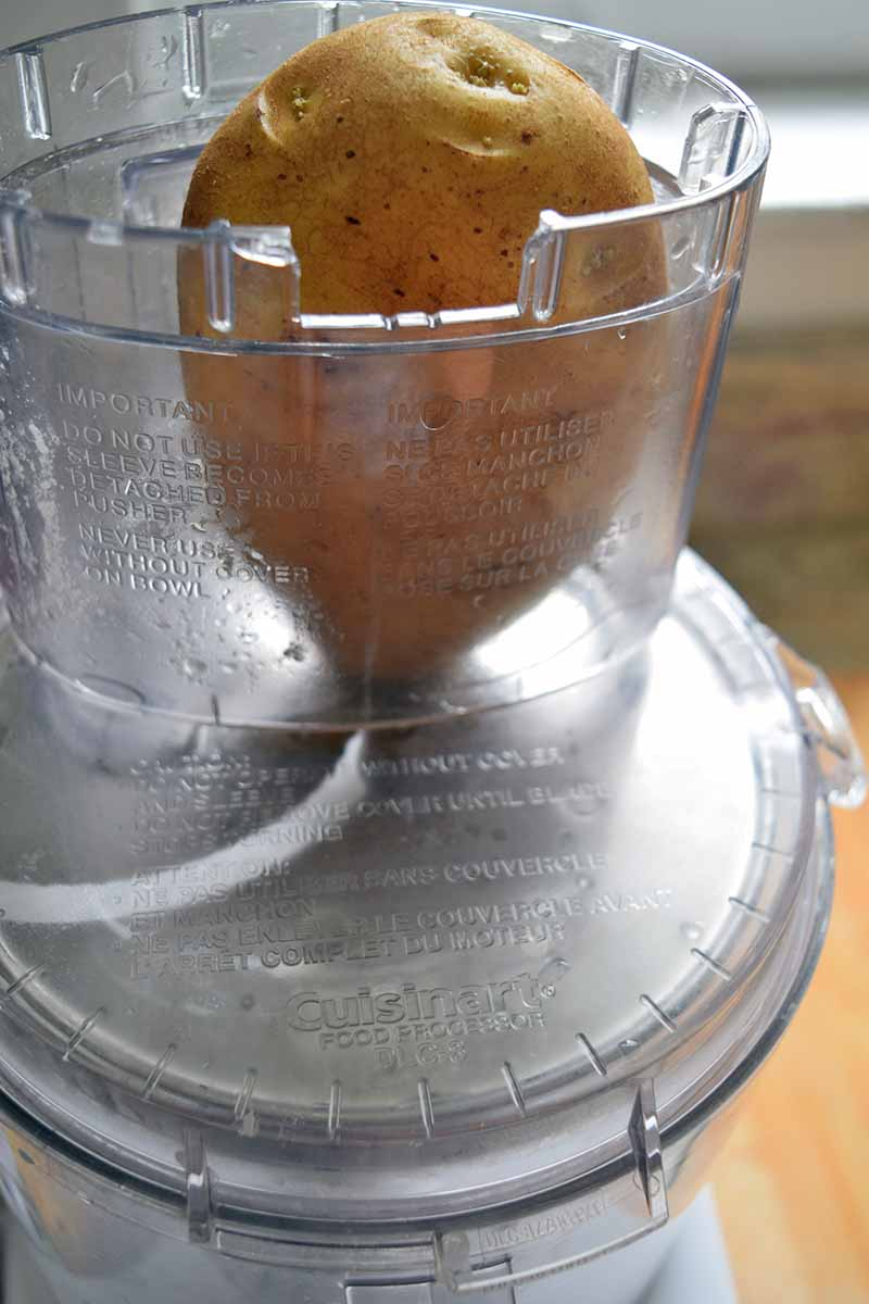 Vertical image of a potato with the skin on in the plastic shut in the top of a food processor with the slicing blade attached, in a kitchen.