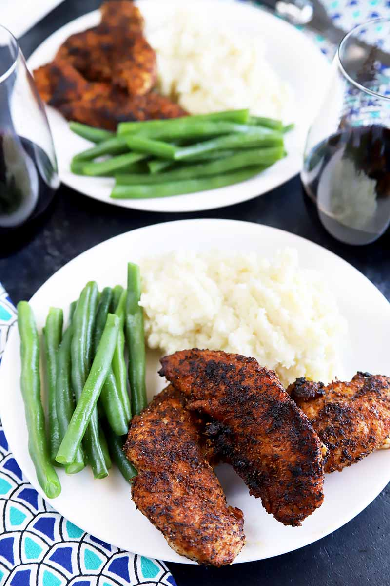 Vertical image of two white plates with cooked and blackened chicken, green beans, and mashed potatoes.