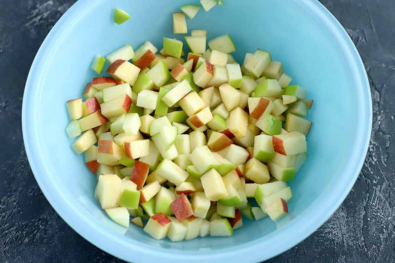 Horizontal image of chopped red and green apple with the peel on in a light blue glass bowl, on a rough gray surface.