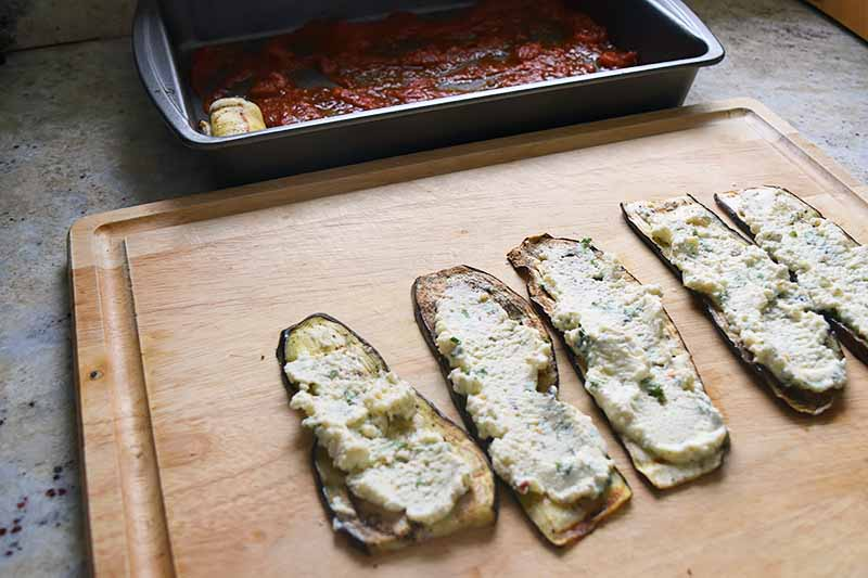 Horizontal image of slices of eggplants topped with ricotta cheese on a cutting board next to a casserole dish.