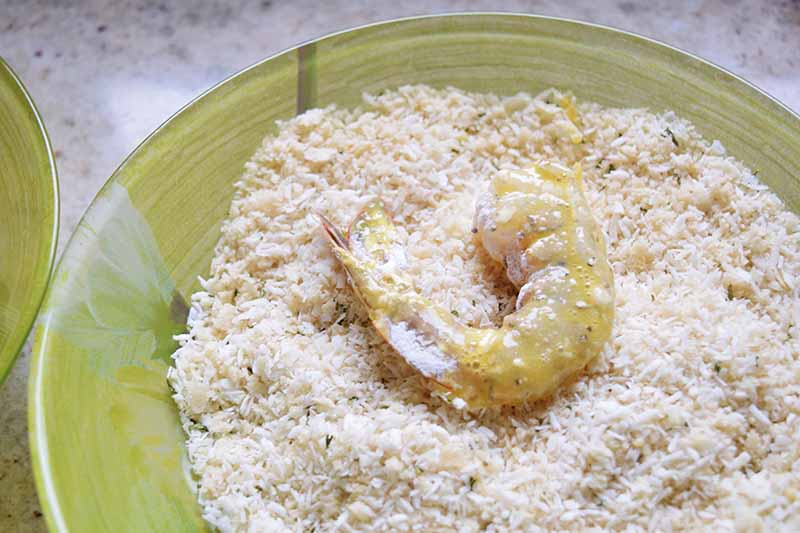 Horizontal overhead image of a light green shallow glass bowl filled with a dry coconut mixture, with one raw shrimp with the tail on being breaded in the bowl, on a white countertop.