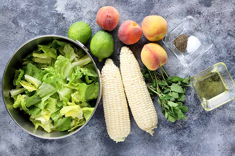 Horizontal image of assorted fresh produce on a gray surface.