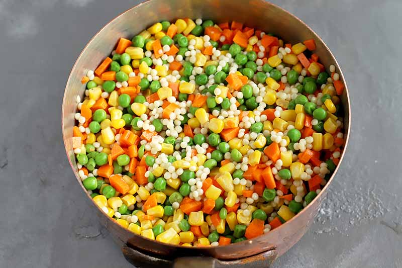 Horizontal image of pot with a mix of peas, corn, carrots, and grains.
