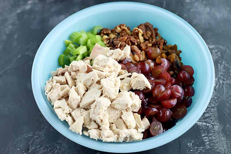 Horizontal oblique overhead shot of a glass bowl of cubed cooked chicken breast, halved red grapes, chopped walnuts, and chopped celery, on a dark gray surface with white speckles.