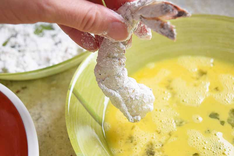 A hand holds a raw shrimp that has been coated with flour, about to dip it into a beaten egg mixture in a shallow light green bowl, with another bowl in the background.